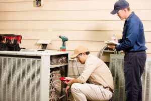 two hvac professionals inspecting the outside unit of an air conditioner
