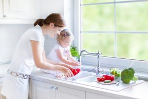 mom and young daughter washing vegetables in kitchen sink