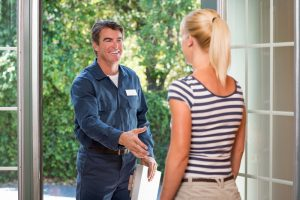 service professional at door about to shake homeowner's hand