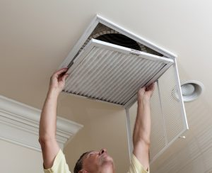 technician taking off vent to access duct