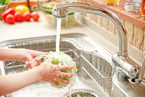 person's hands washing lettuce in the kitchen sink